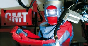 A robot programmer / robot welder uses the touch pendant of a Fronius CMT welding power unit.